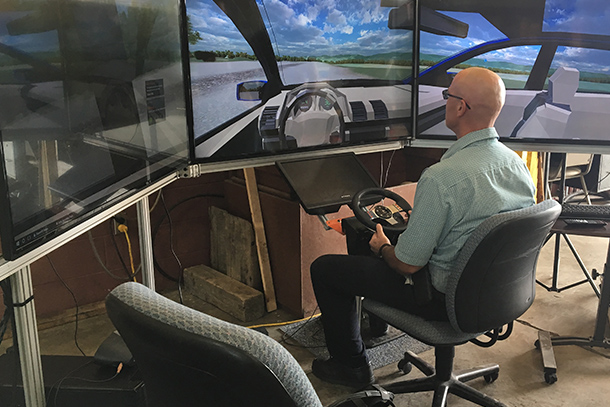 Man sitting in front of three TV screens driving an augmented reality vehicle.